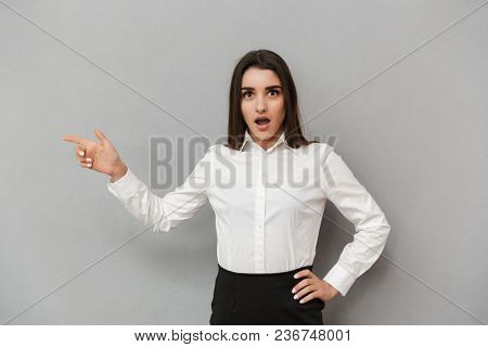 Portrait of excited businesswoman with long brown hair in white shirt pointing finger aside on copyspace with surprise isolated over gray background