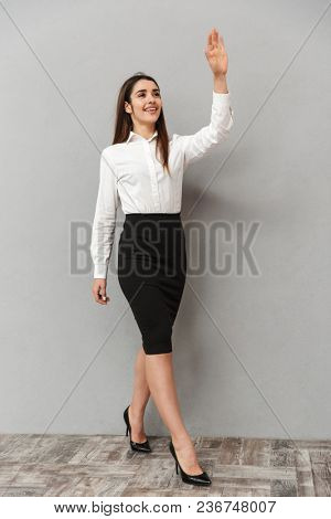 Full length portrait of brunette businesswoman 20s in white shirt and black skirt walking with smile and greeting with waving hand isolated over gray background