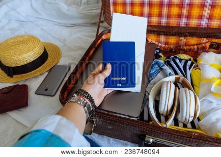 Woman Hands With Watch Put Clothes In Suitcase. Travel Concept. Copy Space. Biometric Passport Lapto