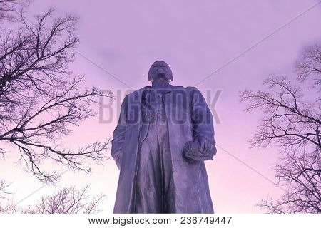 Lenin Monument Closeup On Sunset Background Of Dry Branches And Sky