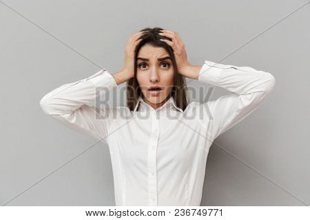 Portrait of frustrated woman in formal dress grabbing her head in panic or problem isolated over gray background