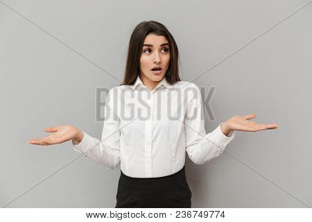 Portrait of charming woman in formal dress throwing up hands like have no idea and looking aside isolated over gray background