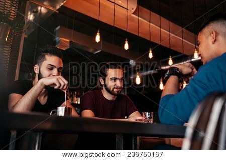 Group Of Mixed Race Young Men Talking And Laughing In Lounge Bar. Multiracial Friends Having Fun In