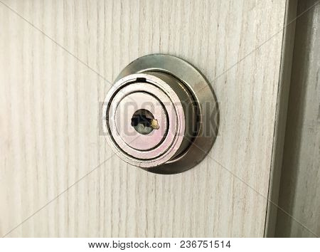 Metal Round Lock In A Wooden Cabinet