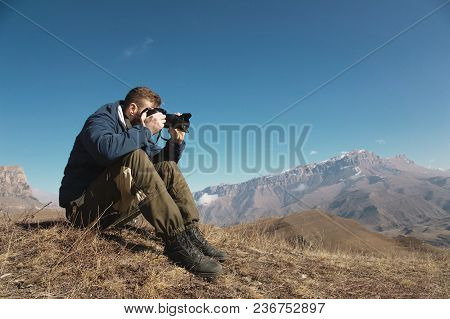 Portrait Of A Bearded Hipster, A Photographer Takes Pictures Of His Dslr Against The Backdrop Of Sno