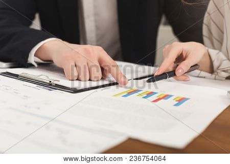 Closeup Of Business Colleagues Hands Checking Diagrams And Results In Documents. Financial Backgroun
