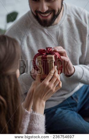 Cropped Image Of Boyfriend Presenting Gift To Girlfriend On 8 March At Home