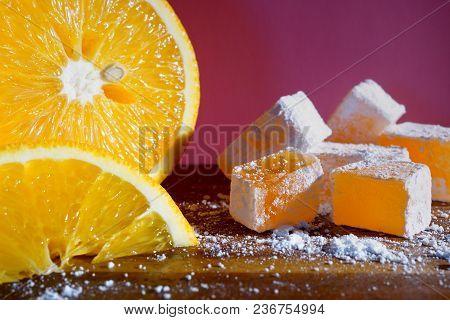 Orange Turkish delight. Rakhat lukum and a big orange. Eastern sweets.