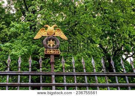 Close Up Golden Double-headed Eagle Mounted On The Gates Of Park In St. Petersburg