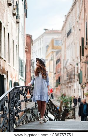 Woman Tourist Travel In Italy. Young Girl With A  Hat In Venice On An Old Street. Girl Traveling To