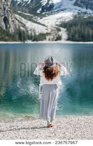 A Girl In A Hat Walks By The Lake In The Background Of The Mountains. Dolomites