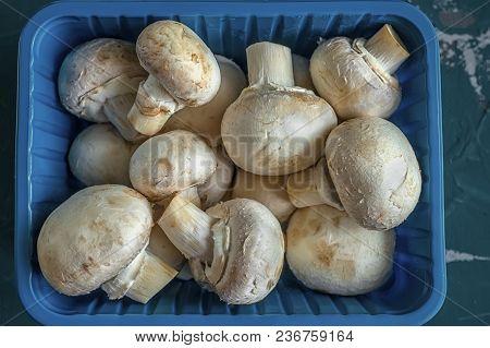 Fresh Mushrooms In A Blue Plastic Box. Dark Background, Close-up.