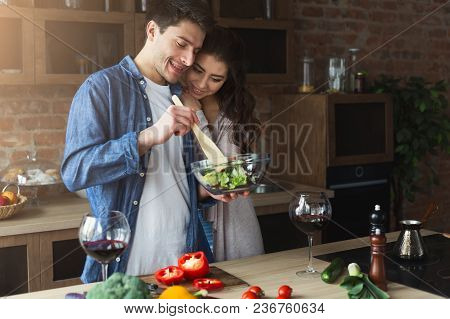 Happy Couple Cooking And Tasting Healthy Food In Their Loft Kitchen At Home. Woman And Man Drinking