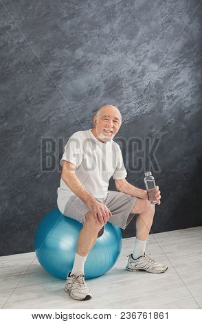 Thirsty Senior Man In Sportswear Relax After Training, Sitting On Fitball, Holding Bottle With Water