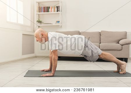 Senior Man Workout At Home. Side View On Mature Caucasian Guy Making Plank Or Push Ups Exercise. Act