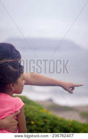 Mother Teaches Her Daughter, While Pointing To The Horizon