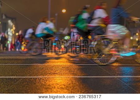 Unidentified Cyclists Riding Bicycle During At Night On A City Street. Healthy Lifestyle Concept. In