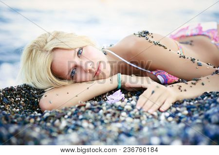Exquisite Beautiful Blond Woman Lies On The Beach From The Pebbles Sunny. Gentle And Bright On A Sea