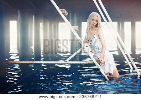 A Refined Beautiful Woman Stands On The Steps Of The Pier And Admires The Evening Sea Light. Well-dr