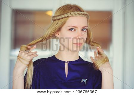 Cute Blonde Woman With Braided Hair Playing, Dressed In A Blue Dress, Beautiful Portrait In The Hous