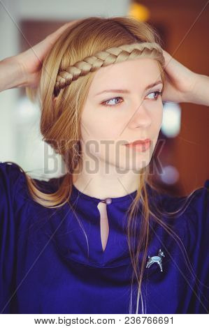 Pretty Blonde Woman With Braided Hair Playing, Hands On Her Head Dressed In A Blue Dress, Beautiful