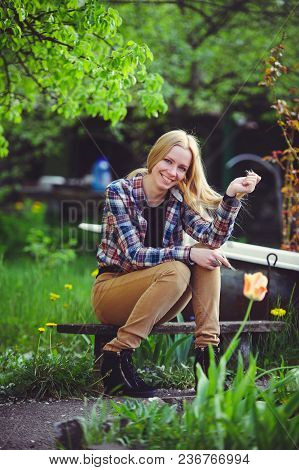 Cute Blonde Woman Sits In A Home Garden, On A Background Of Lots Of Green Trees And Tulips, A Beauti