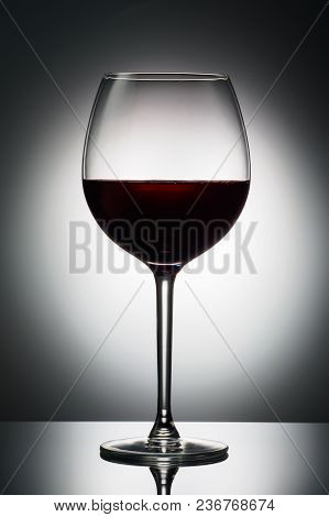 Large Glass Red Wine Shape Of Dark From Grapes Alcoholic Beverage On Luminous Background Advertising