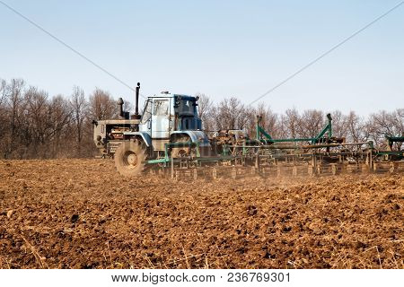 Tractor Preparing Land With Seedbed Cultivator, Spring Sunset At Agricultural Field