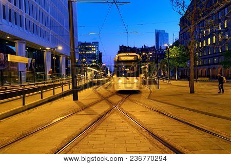Manchester, England. Light Rail Yellow Tram In The City Center Of Manchester, Uk In The Evening. Mot