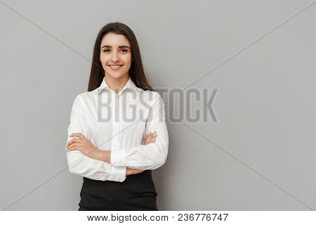 Portrait of caucasian woman with long brown hair in business wear smiling at camera and keeping arms folded isolated over gray background