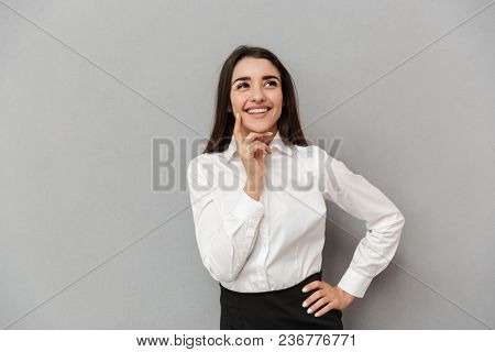Portrait of successful woman 20s in white shirt looking aside and holding finger at cheek while smiling isolated over gray background
