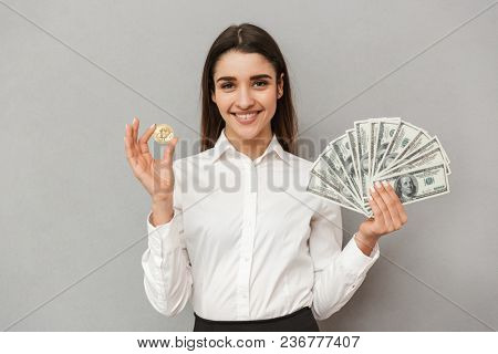 Portrait of beautiful office woman with long brown hair in business wear showing bitcoin and lots of money dollar bills isolated over gray background