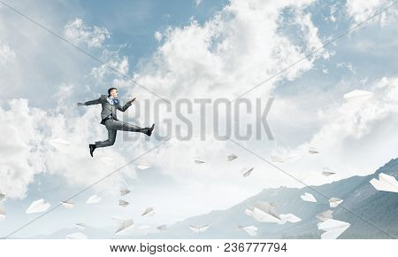 Businessman In Suit Running In The Air Among Flying Paper Planes As Symbol Of Active Life Position.