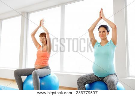 pregnancy, sport, fitness, people and healthy lifestyle concept - group of happy pregnant women sitting on exercise balls in gym