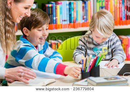 Mom with her two sons spending time in the library reading books