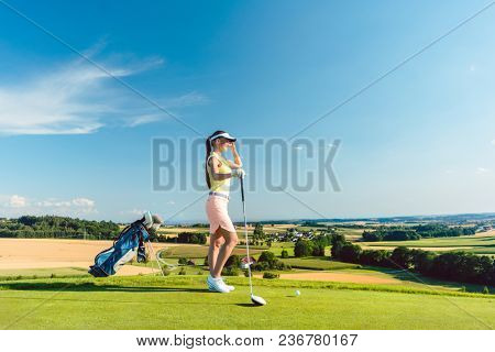 Side view of a fit woman wearing modern golf outfits, while looking at the horizon on the green grass of a golf course in the countryside in a sunny day of summer