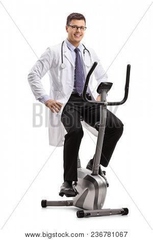 Doctor on a stationary bike looking at the camera and smiling isolated on white background