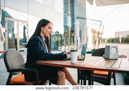 Business woman works on laptop in office. Modern building, financial center, cityscape. Female businessperson in suit at workplace