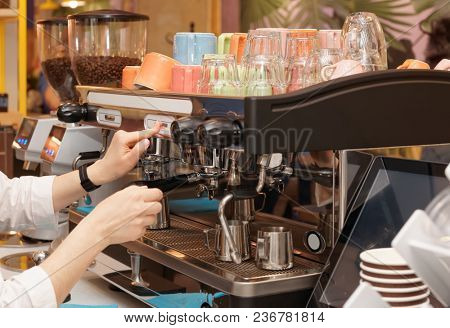 Barista is brewing coffee using professional espresso machine