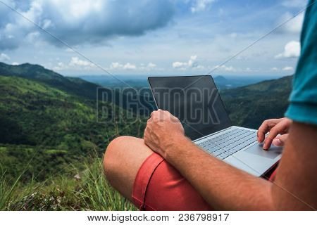 Caucasian Man With Laptop Sitting On The Edge Of Ella Mountain With Stunning Views Of The Valley In