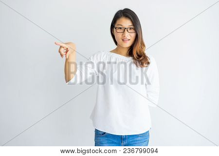Smiling Beautiful Young Asian Woman Asking And Pointing Aside. Positive Confident Student Girl In Ey