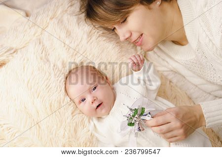 Mother And Newborn Daughter Lie On A Pink Plaid. They Are Dressed In Warm Knitted White Sweaters. Ch
