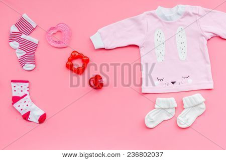 Newborn Baby's Background. Clothes For Small Girl With Booties On Pink Background Top View