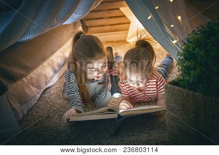 Two cute little children are reading a book with flashlights in tent. Happy girls playing at home. Funny lovely kids having fun in room.