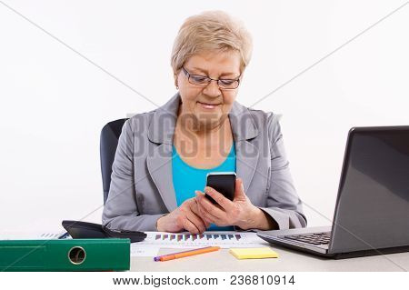 Elderly Senior Business Woman Using Mobile Phone And Working With Financial Charts At Her Desk In Of