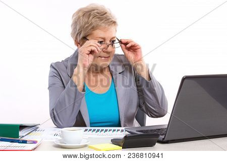 Elderly Senior Business Woman Looking At Laptop Screen And Working With Financial Chart At Desk In O