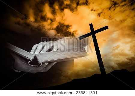 A Man Reading Bible With A Cross