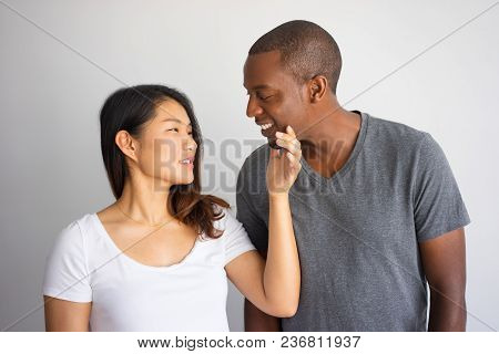 Portrait Of Young Mixed Raced Couple In Love Smiling To Each Other. Young Asian Woman Touching Chin