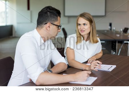 Confident Businesswoman Talking At Meeting To Male Colleague. Young Caucasian Businesswoman And Busi