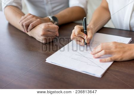 Hand Of Female Hr Manager Filling In Form At Interview With Male Candidate. Close-up Of Young Caucas